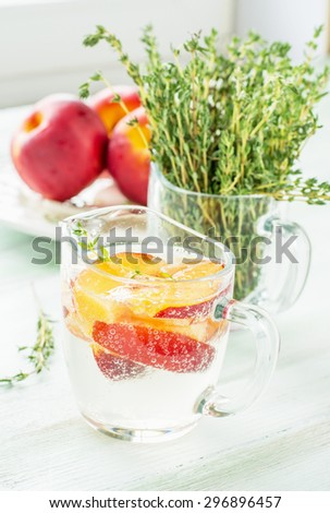 A refreshing fizzy drink with slices of peach, nectarine, sprigs of thyme on the background of the bouquet of thyme and fresh fruit. selective Focus - stock photo