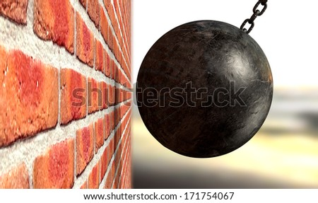 A regular metal wrecking ball attached to a chain hitting and breaking a face brick - stock photo