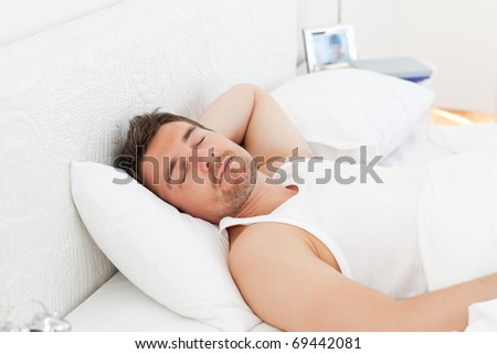 A relaxed man in his bed before waking up in his bedroom - stock photo