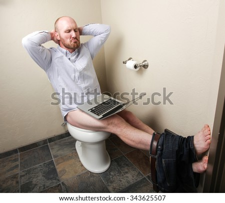 A relaxed man looking at his computer while on the toilet - stock photo