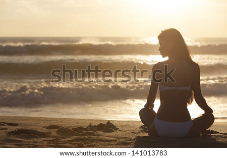 A relaxed sexy young brunette woman or girl wearing a bikini sitting on a deserted tropical beach at sunset or sunrise - stock photo