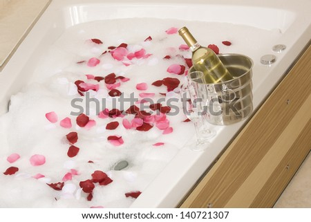 A relaxing bath with rose petals ,wine and glassess - stock photo