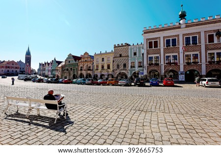 A relaxing leisure moment under the sun at Telc (Teltsch) Old Town Square with colorful historic houses of renaissance and baroque styles, a beautiful UNESCO town in Czech Republic, Europe  - stock photo