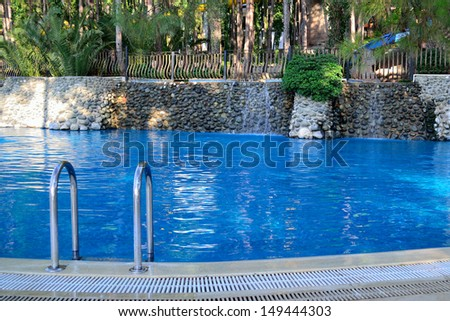 a relaxing open-air swimming pool in the garden - stock photo