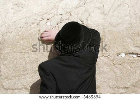 A religious Jew prays at the western wall - stock photo
