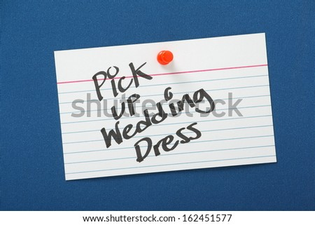 A reminder to Pick Up Wedding Dress written on a white note card and pinned to a blue notice board - stock photo