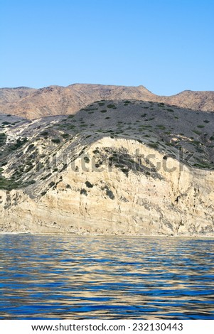 A remote island in the Channel Islands of California shows the geology of rugged, diverse terrain framed against deep turquoise water and a vibrant blue sky. - stock photo
