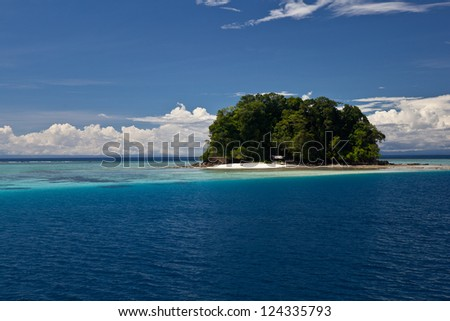 A remote tropical, South Pacific island is surrounded by clear water and diverse coral reefs in the Solomon Islands. - stock photo