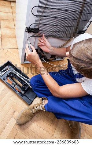 A repairman sitting on the floor fixing a fridge with special tools - stock photo