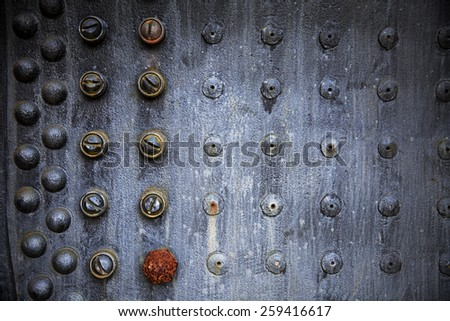 A repeating pattern of rusting rivets on the outside of an old steam engine locomotive forms a unique background. - stock photo