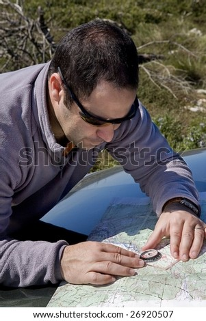 A rescue crew member using a field map and a compass to orienteering - stock photo