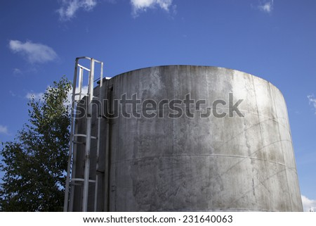 a reservoir for oil on the sky background - stock photo