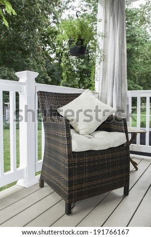 A resin wicker chair sits on a covered deck with cream colored cushion and pillows; curtains hang behind; plants hang from above - stock photo