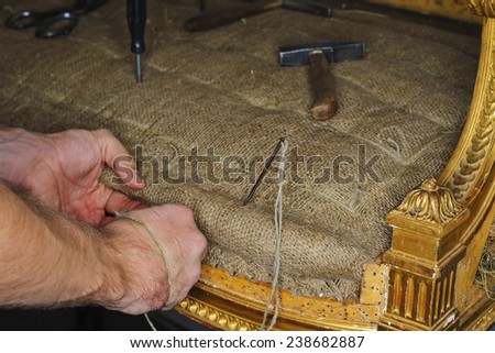 a restorer renews the upholstery of antique sofa - stock photo