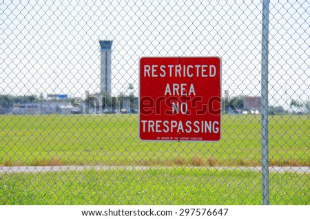 A RESTRICTED AREA NO TRESPASSING sign on a fence at an airport with the air traffic control tower in the background - stock photo