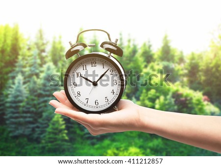 A retro alarm-clock on female hand, forest background - stock photo