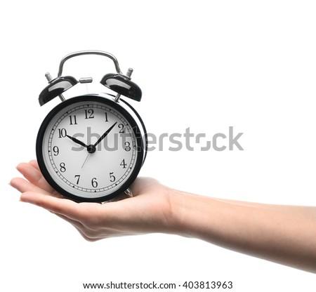 A retro alarm-clock on female hand, isolated on white - stock photo