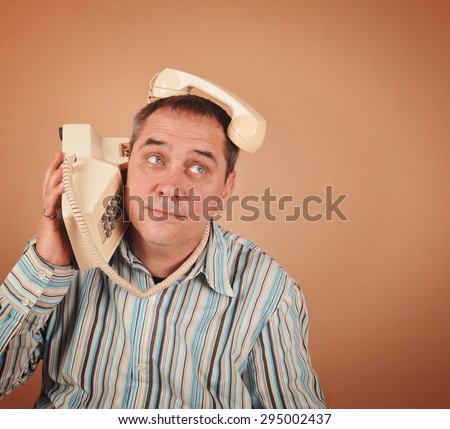 A retro 1970's man is using an old telephone in an unusual funny way on an isolated background for a communication or technology concept. - stock photo