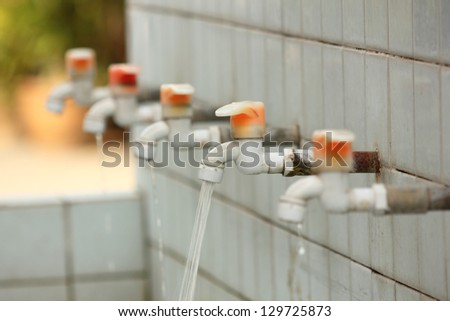 A retro sink tap and faucet with running water. - stock photo