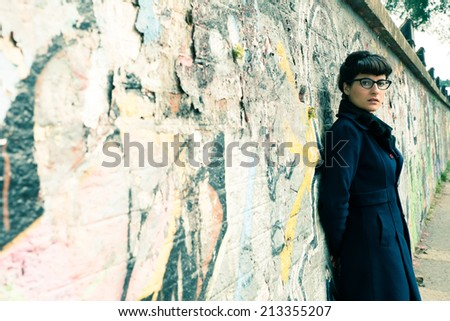 A retro styled girl leaning against a graffiti sprayed wall in a urban environment. - stock photo