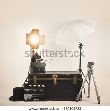 A retro vintage camera with studio lights and various photography lighting equipment for a director or film concept. - stock photo