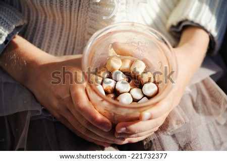 A rich cup of hot chocolate with small marshmallow in kid hands - stock photo