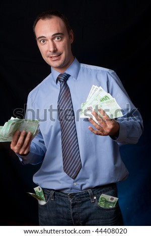 A rich man shows his earnings with an expression of success. Wads of money in his hands and pockets.Conceptual image for business success, rich people, income, ... - stock photo