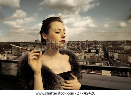 a rich woman with fur and cigarette on top of a building - stock photo
