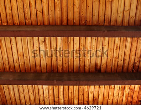 A richly colored wooden slat ceiling with exposed beams - stock photo
