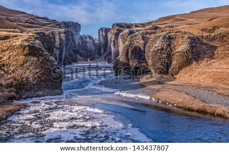 A river flows and cuts through an ancient gorge in Iceland. - stock photo