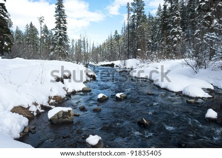 A river in the mountains with snow along the banks. - stock photo