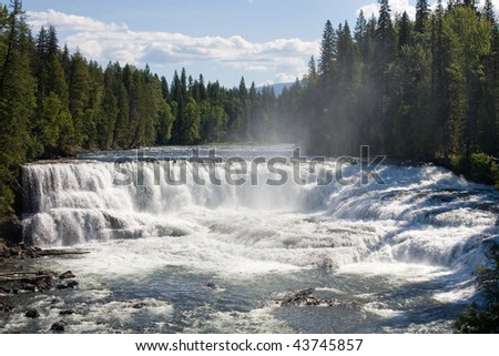 A river produced a wide waterfall in a forest. Dawson Falls in  Wells Gray Park, Canada - stock photo