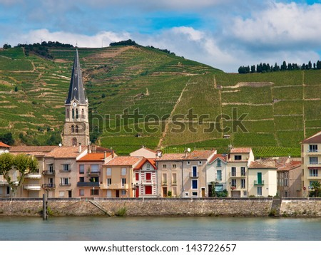 A riverside Village and Vineyards on the Hills of the Cote du Rhone Area in France - stock photo