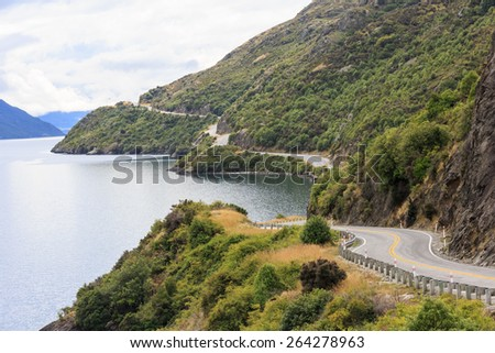 A road along Lake Wakatipu under a cloudy sky in New Zealand - stock photo