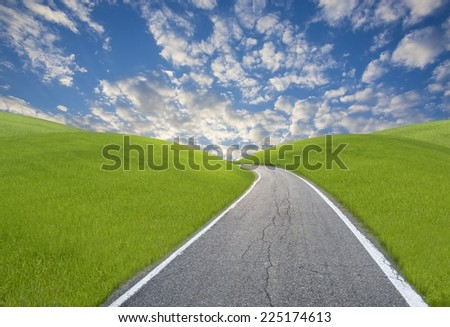 A road among green hills with a blue sky in background - stock photo