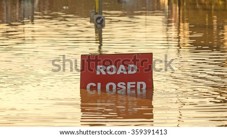 A 'Road Closed' sign partially covered in flood water lit by the evening sun - stock photo