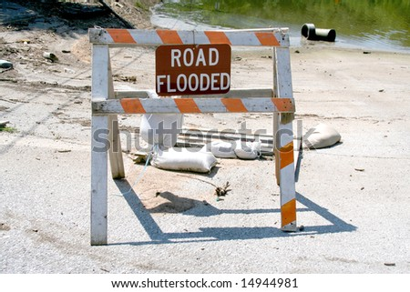 "A ""Road Flooded"" Sign in front of flood waters that have hammered the midwestern U.S. - stock photo"