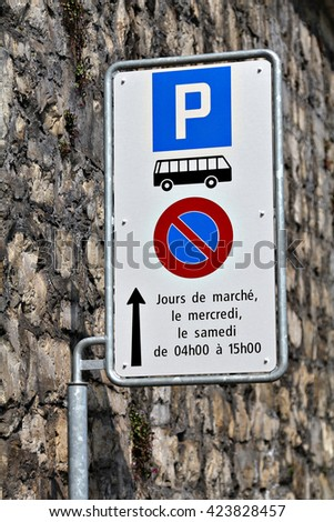 A road sign indicates that parking is reserved for buses. A sign on a post pole next to the road. Traffic road sign. Blue signage signpost. - stock photo
