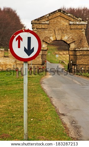 A road sign indicating which direction has priority, showing the narrow arch they must go through - stock photo