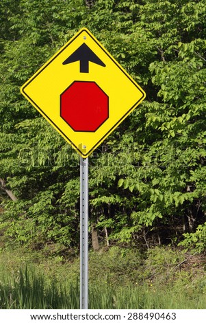 A road sign warning drivers of a stop ahead. - stock photo