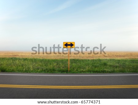 A road sign with arrows pointing in two directions along a quiet country road. - stock photo