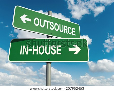A road sign with outsource inhouse words on sky background  - stock photo