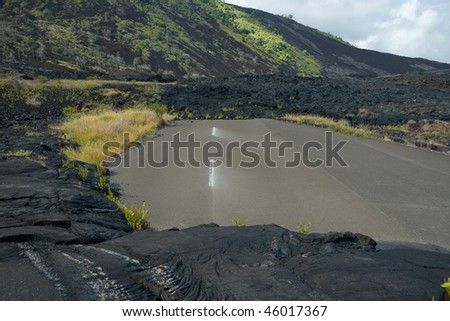 A road to nowhere. Flowing lava has blocked this road on Hawaii's Big Island - stock photo