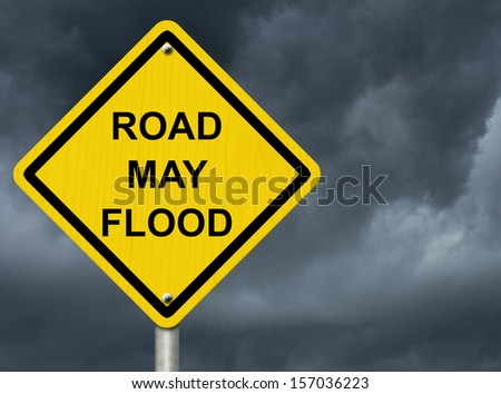 A road warning sign against a stormy sky with words Road May Flood, Flood Warning - stock photo