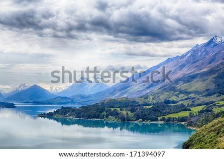 A road winds around Lake Wakatipu near Queenstown, New Zealand - stock photo