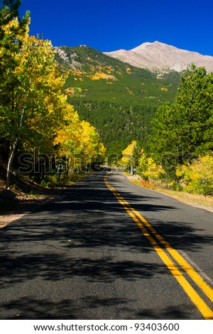 A road winds through the gold Aspen trees as the gorgeous blue Colorado sky and Rocky Mountains frame the scene - stock photo