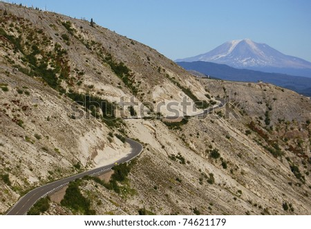 A road winds through the May 18, 1980 Mount St. Helens blast zone with Mount Adams looming in the background. - stock photo