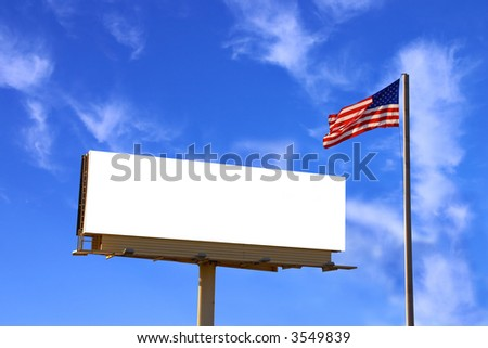 A roadside billboard with an American Flag next to it. The sky has been carefully replaced with another similarly lit sky but with more clouds - stock photo