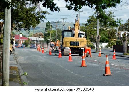 a roadworks gang repairing pot holed suburban streets - stock photo