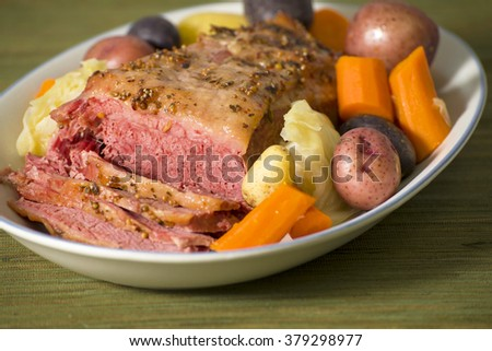 A roasted corned beef brisket, heavily seasoned and sliced, surrounded by carrots, potatoes and cabbage; focus on the front to emphasize the texture of the meat, seasonings, and the vegetables - stock photo
